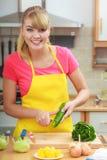 Mujer que prepara el pepino de la peladura de la ensalada de las verduras Fotografía de archivo