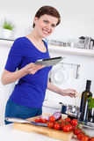 Mujer que prepara el plato de las pastas y que comprueba la receta en una tableta Fotos de archivo libres de regalías
