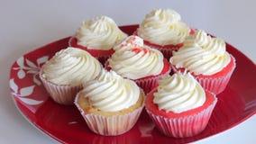 Mujer que prepara el terciopelo rojo de la magdalena Asperje la crema con las migas Las tortas acabadas est?n en la placa metrajes