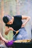 Mujer que prepara la carne en la parrilla Foto de archivo libre de regalías