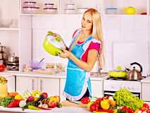Mujer que prepara la comida en la cocina. Imagen de archivo
