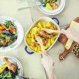 Mujer que prepara la comida para la cena Pollo asado con el acompañamiento de la patata Foto de archivo