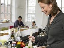 Mujer que prepara la ensalada con la familia que se sienta en fondo en casa Imagen de archivo libre de regalías