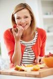 Mujer que prepara la ensalada de fruta en cocina Fotografía de archivo libre de regalías