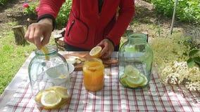 Mujer que prepara la limonada sabrosa con una flor más vieja metrajes