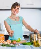 Mujer que prepara la sopa vegetariana en cocina residencial Imágenes de archivo libres de regalías