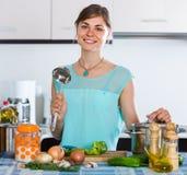 Mujer que prepara la sopa vegetariana en cocina residencial Foto de archivo