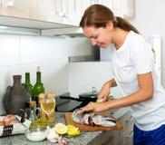 Mujer que prepara los bacalaos frescos en la cocina Imagen de archivo libre de regalías