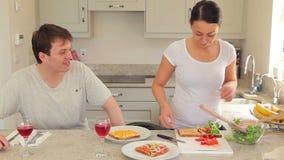Mujer que prepara los sandwches para el almuerzo con el marido almacen de metraje de vídeo