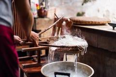 Mujer que prepara los tallarines de arroz tradicionalmente en casa imagenes de archivo