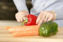 Mujer que prepara una comida en la cocina Imágenes de archivo libres de regalías