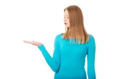 Mujer que presenta algo en la palma Fotografía de archivo