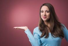 Mujer que presenta algo en su lado Imágenes de archivo libres de regalías