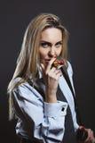 Mujer que presenta con el lápiz labial como cigarro Imagen de archivo