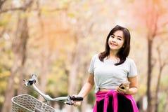 Mujer que presenta con el teléfono y la bicicleta imagen de archivo libre de regalías
