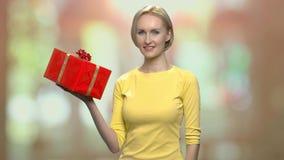 Mujer que presenta con la caja de regalo metrajes