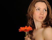 Mujer que presenta con la flor Imagen de archivo