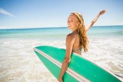 Mujer que presenta con la tabla hawaiana en la playa Imágenes de archivo libres de regalías