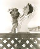 Mujer que presenta con su Airedale en la playa foto de archivo libre de regalías