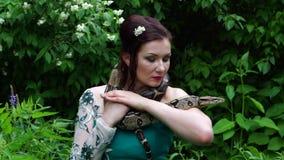 Mujer que presenta con una serpiente alrededor de su cuello almacen de metraje de vídeo