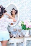 Mujer que presenta delante de un espejo en bigudíes de pelo Imagen de archivo
