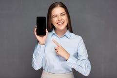 Mujer que presenta el teléfono elegante con la pantalla vacía y que señala fing Imagen de archivo