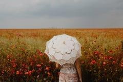 Mujer que presenta en campo de las amapolas con el paraguas Interpreta artístico Fotografía de archivo