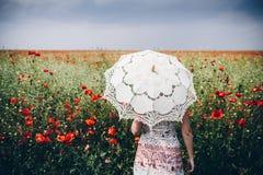 Mujer que presenta en campo de las amapolas con el paraguas Interpreta artístico Foto de archivo