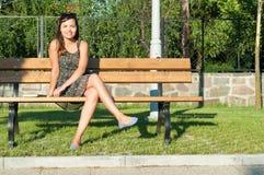 Mujer que presenta en el parque que se sienta en banco y la sonrisa Foto de archivo libre de regalías