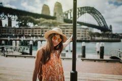 Mujer que presenta en la ciudad de Sydney con el puente del puerto en el fondo imagen de archivo