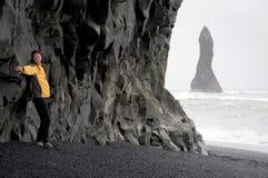 Mujer que presenta en la playa negra de la arena, Islandia Foto de archivo