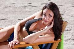 Mujer que presenta en una silla de playa fotografía de archivo