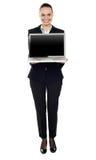 Mujer que presenta la nueva computadora portátil Imagen de archivo