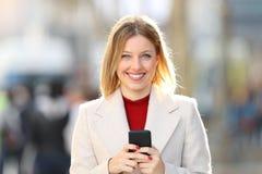 Mujer que presenta mirándole que sostiene un teléfono elegante Imagen de archivo