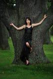 Mujer que presenta por el árbol Imagenes de archivo