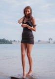 Mujer que presenta por el mar Imagen de archivo