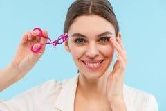 Mujer que presenta sobre el bigudí azul del latigazo de la tenencia del fondo que hace maquillaje imagen de archivo