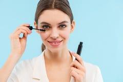 Mujer que presenta sobre el rimel azul del latigazo de la tenencia del fondo que hace maquillaje imagen de archivo libre de regalías
