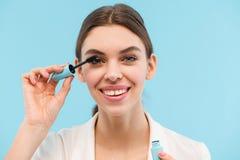 Mujer que presenta sobre el rimel azul del latigazo de la tenencia del fondo que hace maquillaje foto de archivo