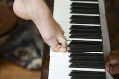 Mujer que presiona el piano Imagen de archivo