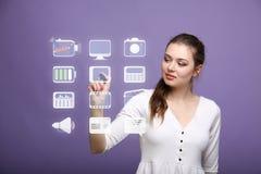 Mujer que presiona iconos de las multimedias y del entretenimiento en un fondo virtual Imagen de archivo libre de regalías