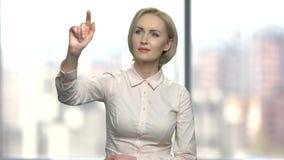 Mujer que presiona y que birla una pantalla virtual invisible almacen de metraje de vídeo