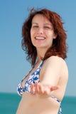 Mujer que presta una mano en una playa Fotos de archivo libres de regalías