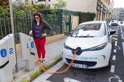 Mujer que programa una estación de carga del zen para cargar a Renault Zoe Foto de archivo