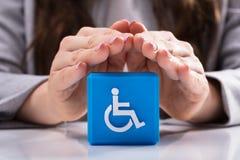 Mujer que protege el bloque c?bico con el icono discapacitado de la desventaja imágenes de archivo libres de regalías