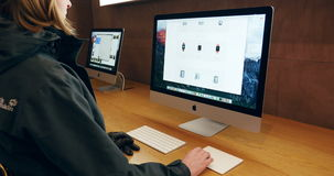 Mujer que prueba el nuevo ordenador de la exhibición de la retina de iMac metrajes