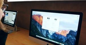 Mujer que prueba la nueva exhibición de la retina de iMac con el nuevo cojín del teclado y de Apple Touch de Apple almacen de video