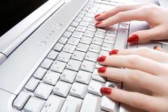 Mujer que pulsa en el teclado de la computadora portátil Foto de archivo
