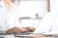 Mujer que pulsa en el teclado de la computadora portátil Imagen de archivo libre de regalías