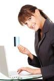 Mujer que pulsa en el teclado y que se considera de la tarjeta de crédito Fotografía de archivo